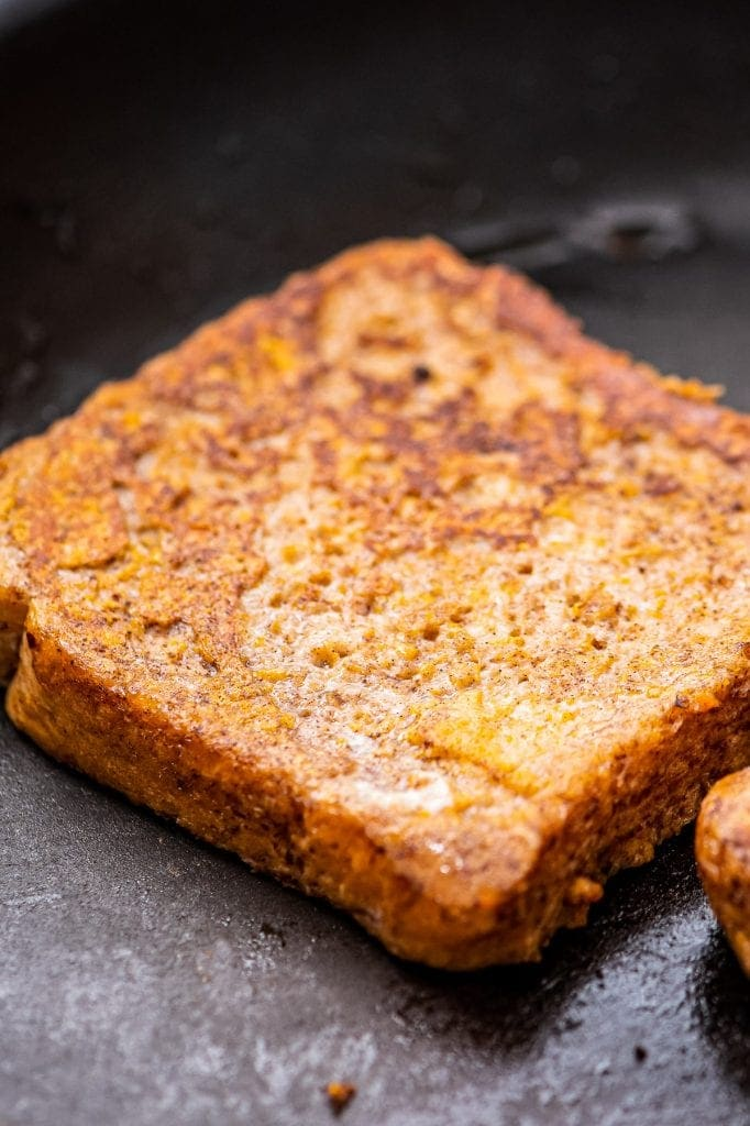 Close up of a piece of pumpkin french toast in skillet
