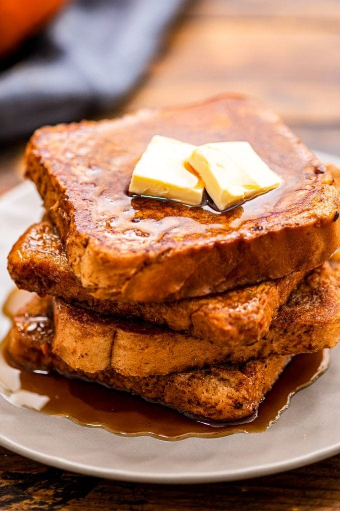 A white plate with a stack of pumpkin french toast topped with butter and syrup