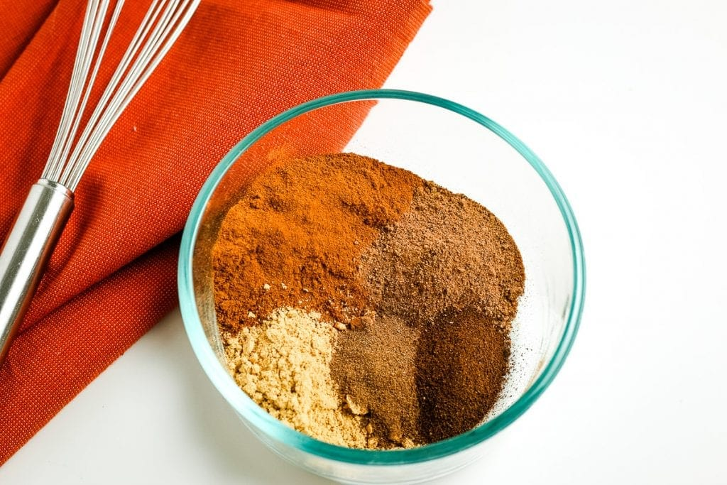 A glass bowl with spices in it to make pumpkin pie spice before mixing it together.