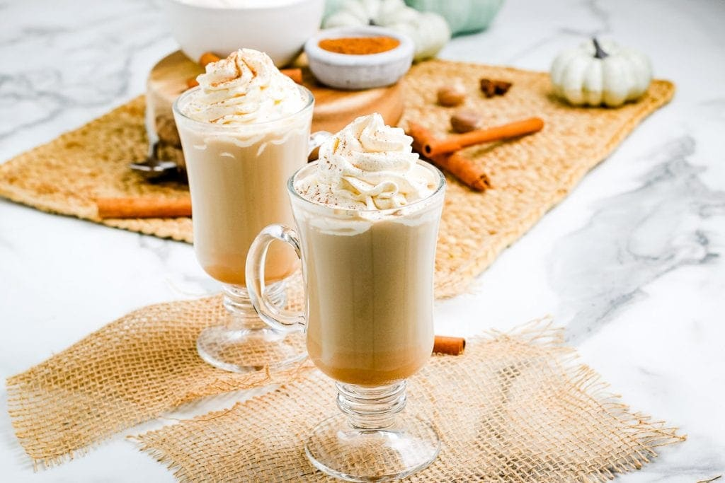 Pumpkin Spice Latte in tall glass mugs with whipped cream and cinnamon on top.