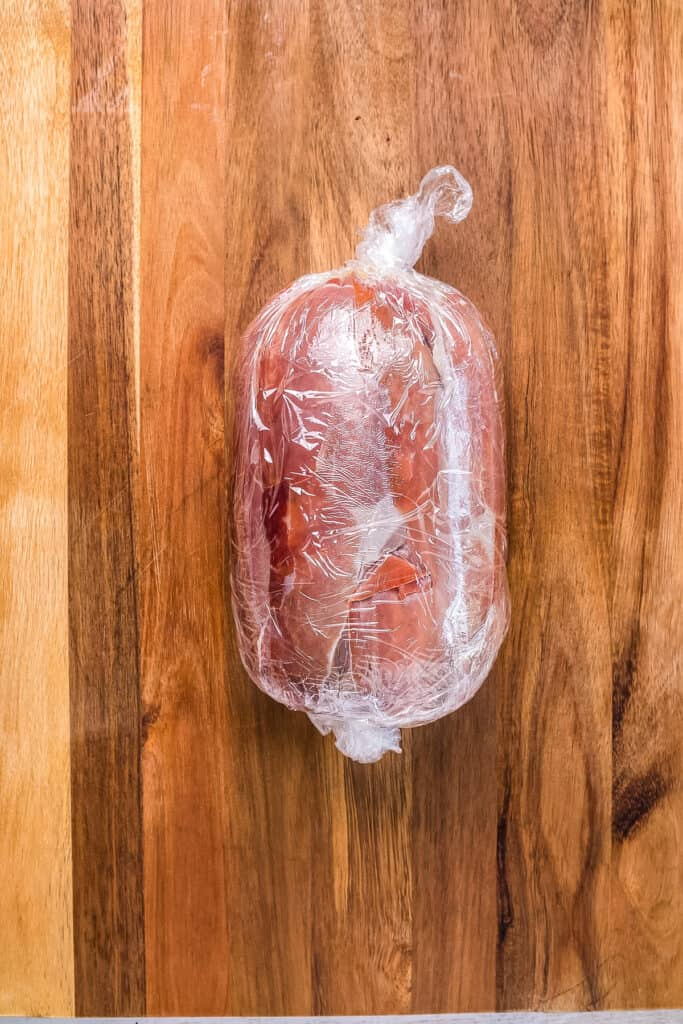 Prosciutto wrapped beef tenderloin wrapped in plastic wrap