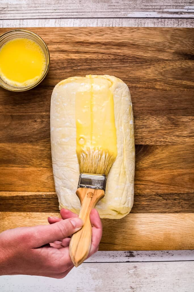 Hand brushing butter on puff pastry with pastry brush