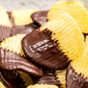 A stack of chocolate covered potato chips on plate