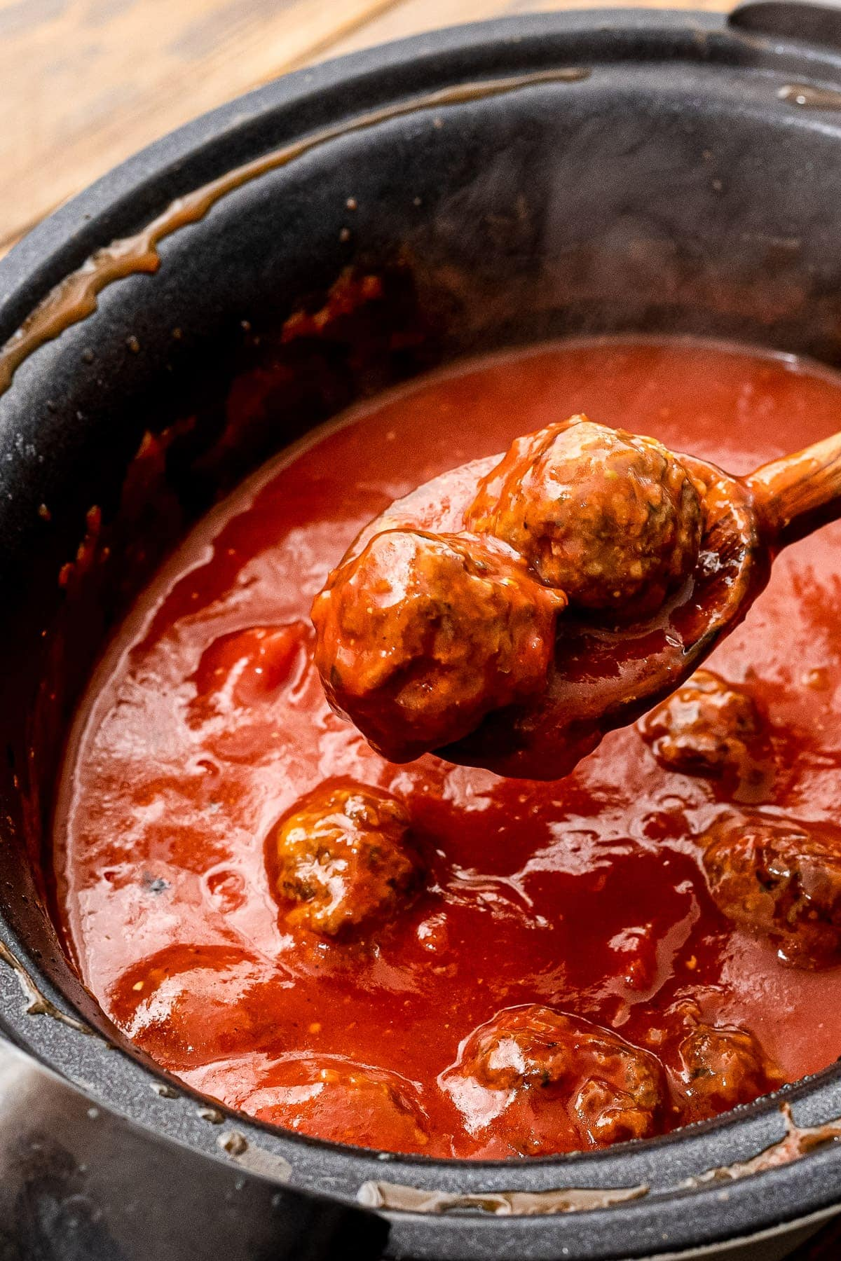 Wooden spoon scooping meatballs out of crock pot with spaghetti sauce in it.