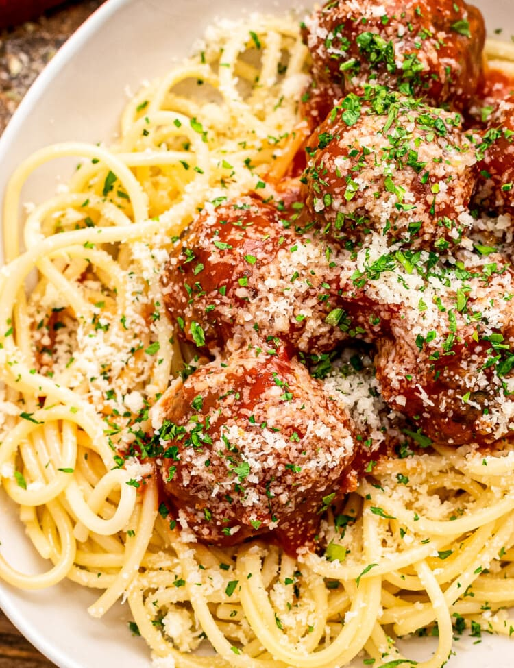 White plate with bed of spaghetti noodles topped with meatballs and sauce.
