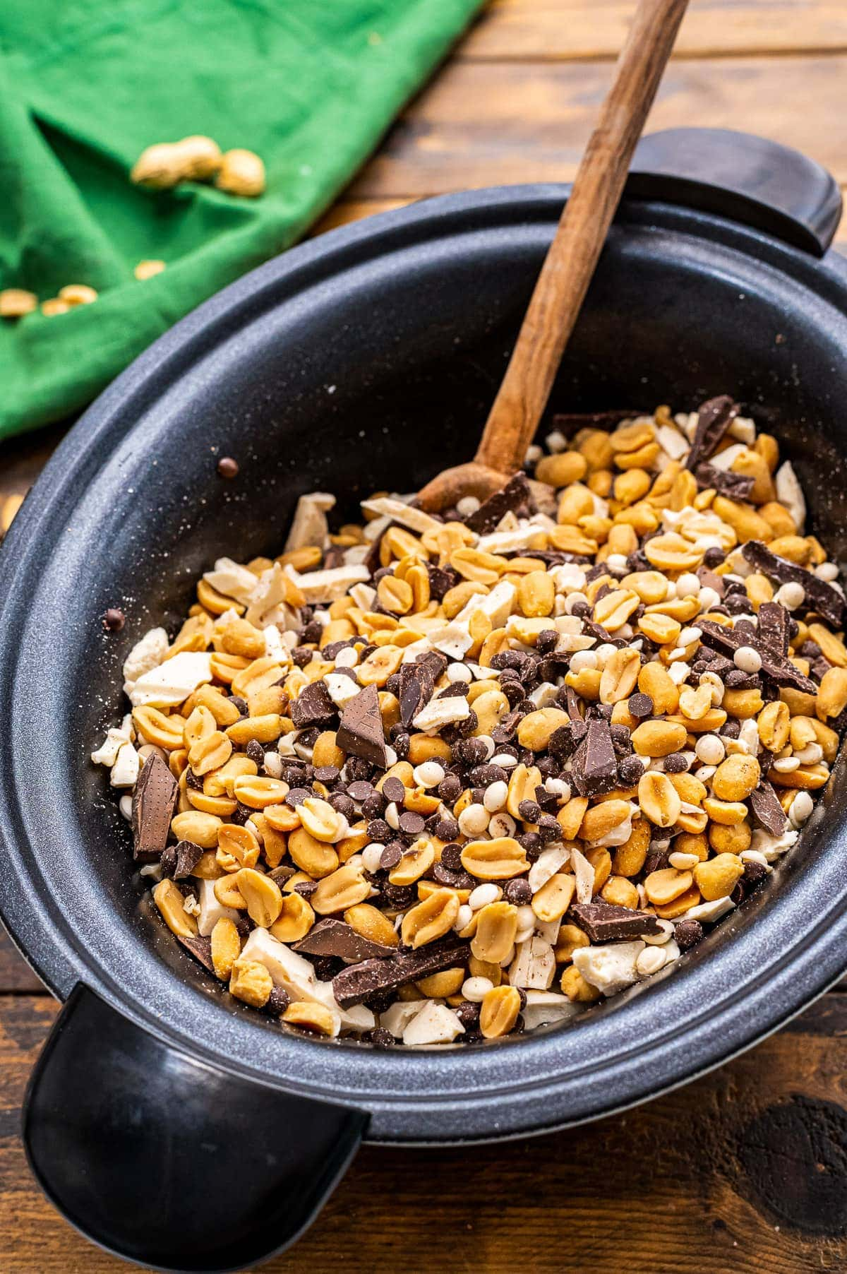 Crock Pot with ingredients for peanut clusters stirred together.