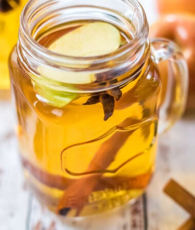 Close up photo of spiked apple cider in glass mason jar mug
