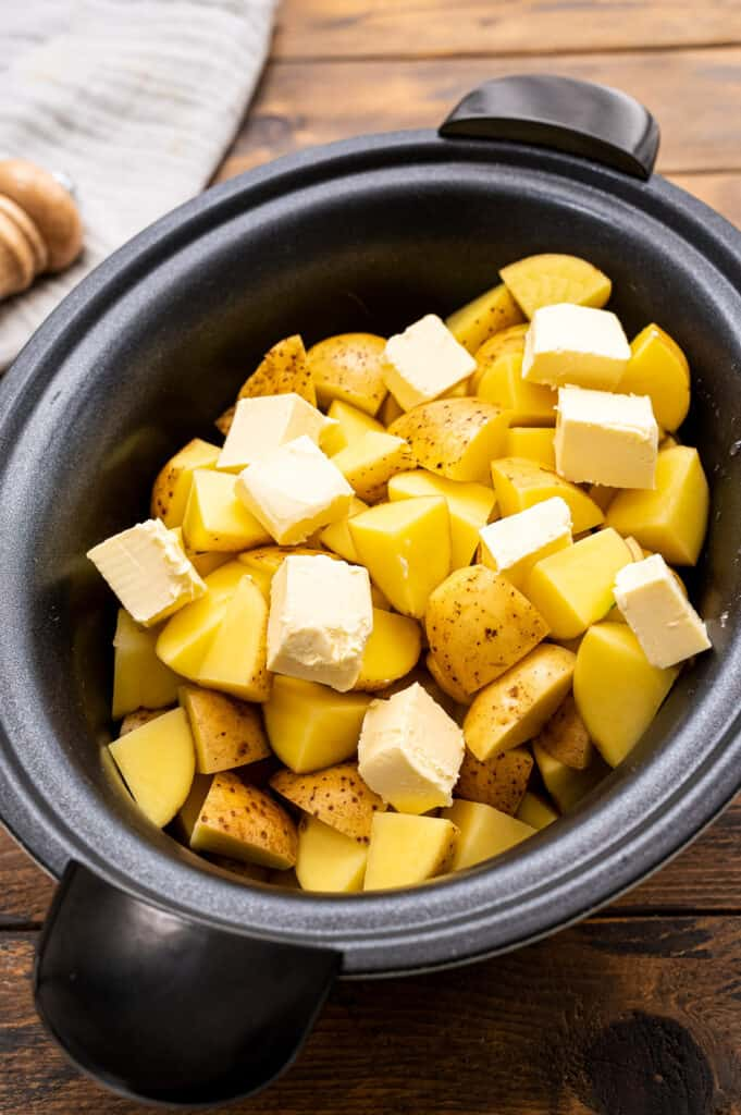 Potatoes and butter in black crock pot.