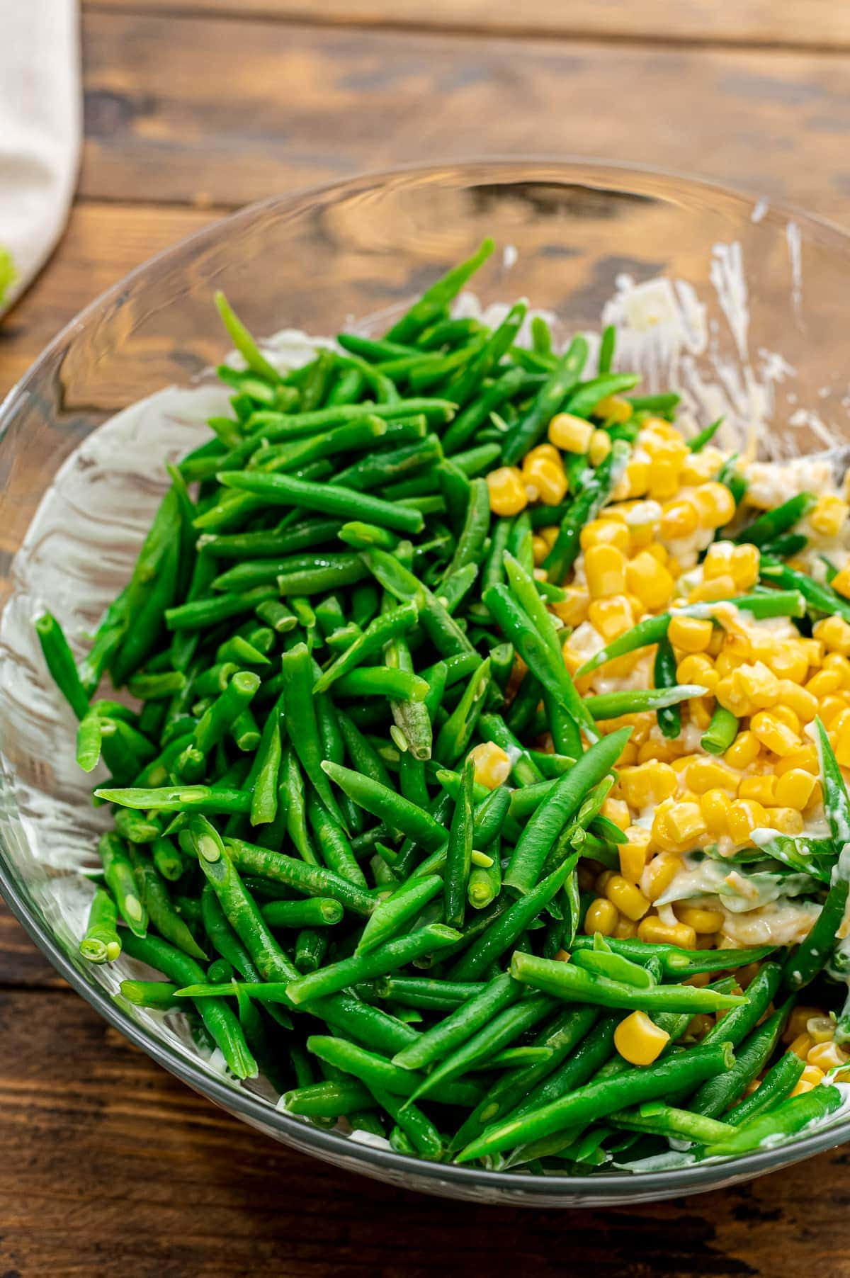 Glass bowl with corn and green beans added to soup mixture for casserole