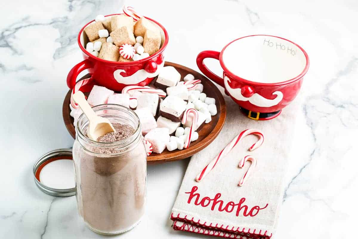 Marble background with homemade hot chocolate mix in container and festive decor