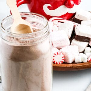 Hot Chocolate Mix in glass jar with a little scoop and festive decor in background