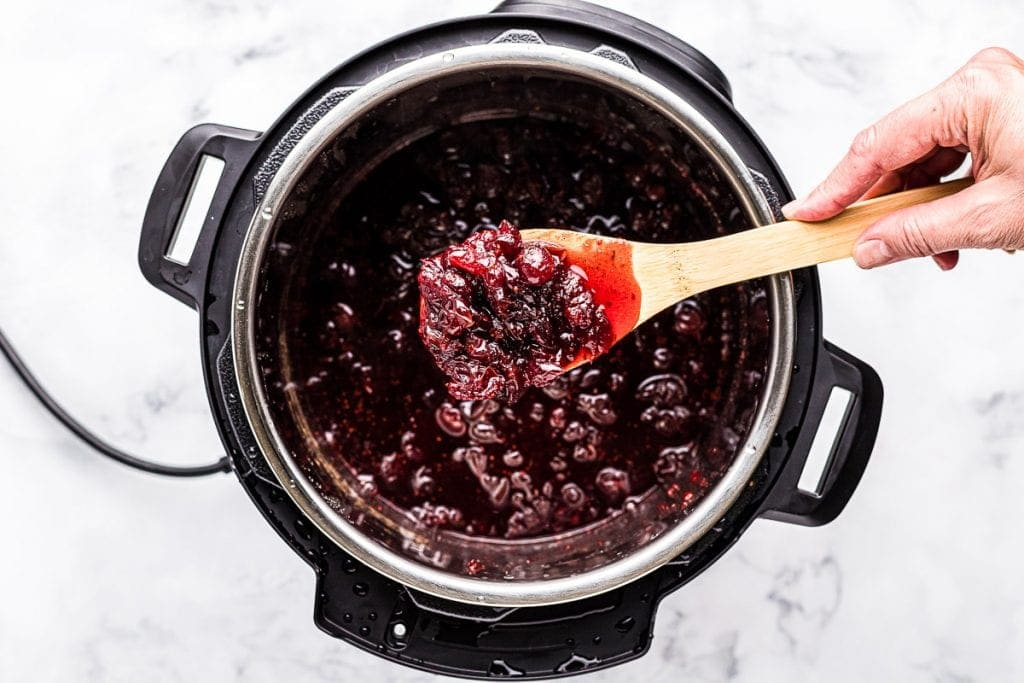 Spoon with Instant Pot cranberry sauce on it over the instant pot.