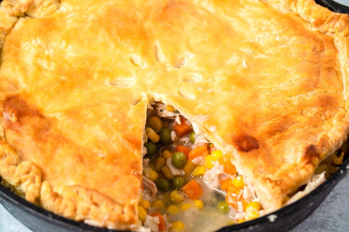Turkey pot pie in cast iron skillet with slice taken out.