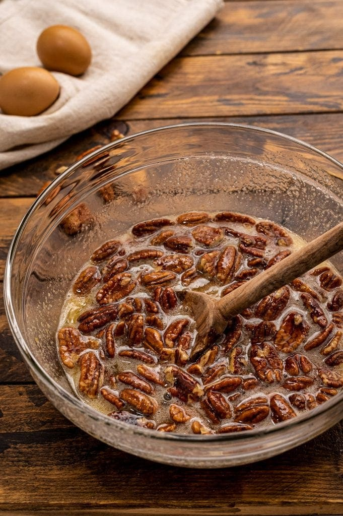 Glass bowl with ingredients for pecan pie after stirring.