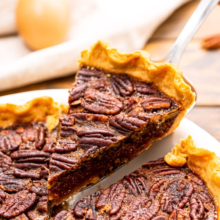 Piece of pecan pie being lifted out of pie in a white pie dish.