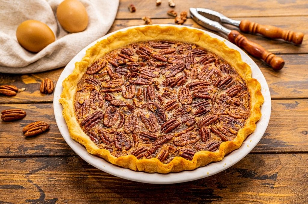 Pecan Pie in a white baking dish on wood background