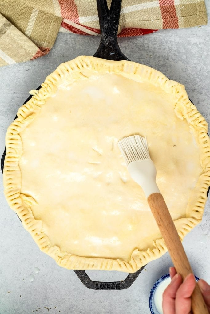 Pastry brush brushing butter over puff pastry crust on pot pie