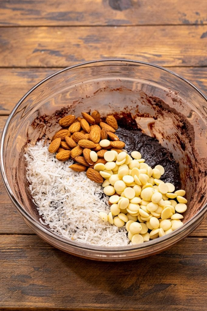 Glass bowl with ingredients to make Almond Joy Cookies before mixing