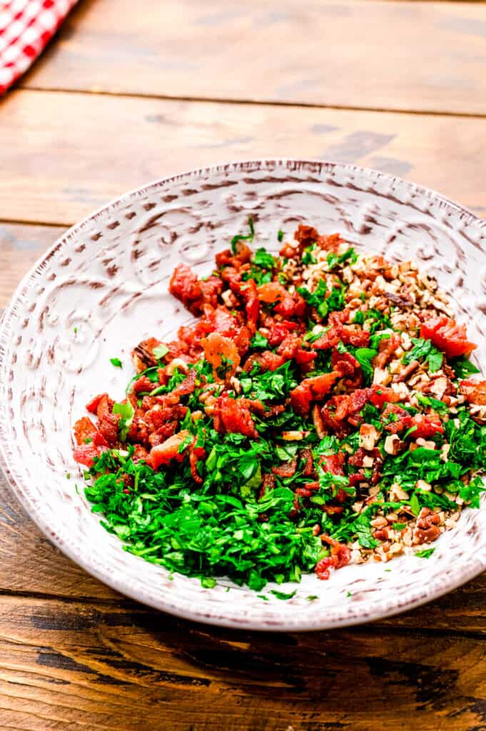 Bowl with bacon, nuts and fresh parsley combined.