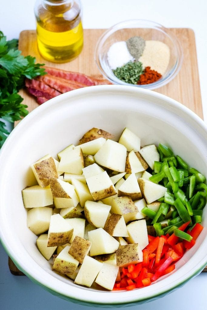 White bowl with diced potatoes, red and green peppers before stirring.