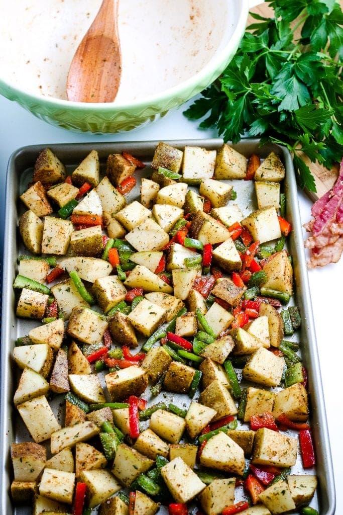 Sheet pan with breakfast potato ingredients on it before baking