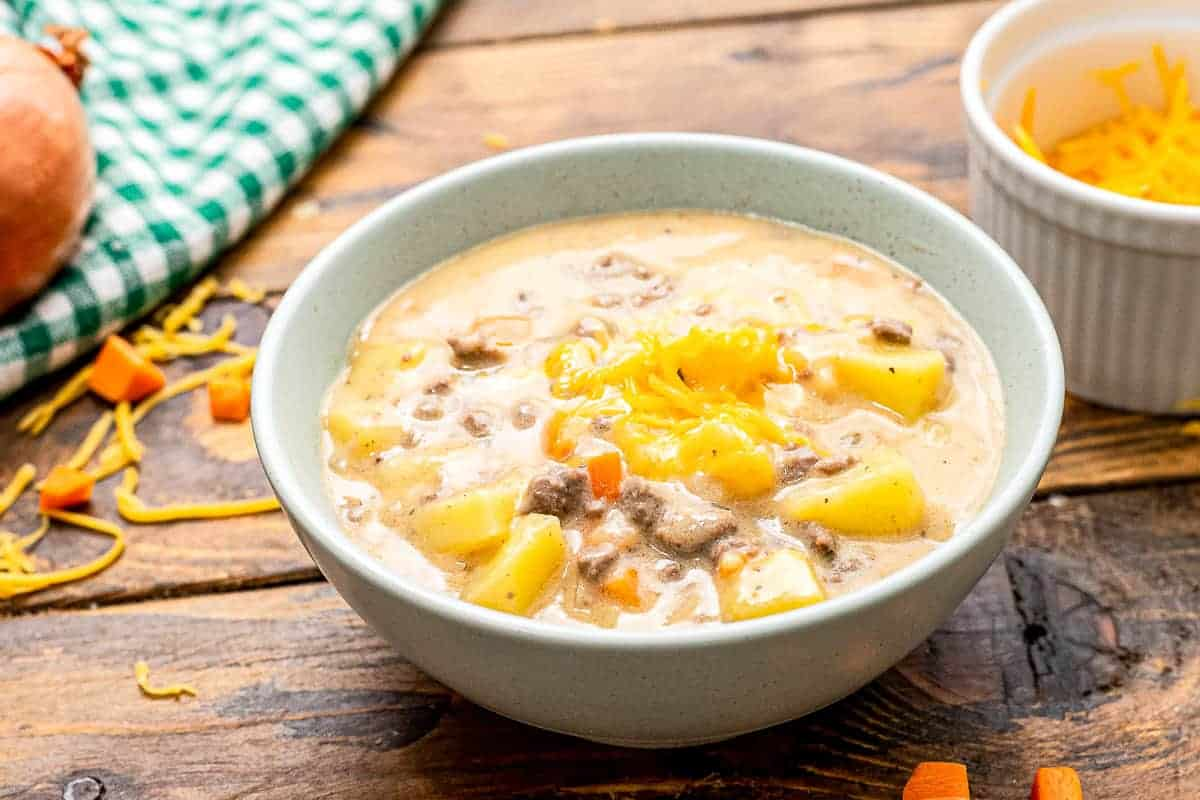 Bowl of cheeseburger soup on wooden background