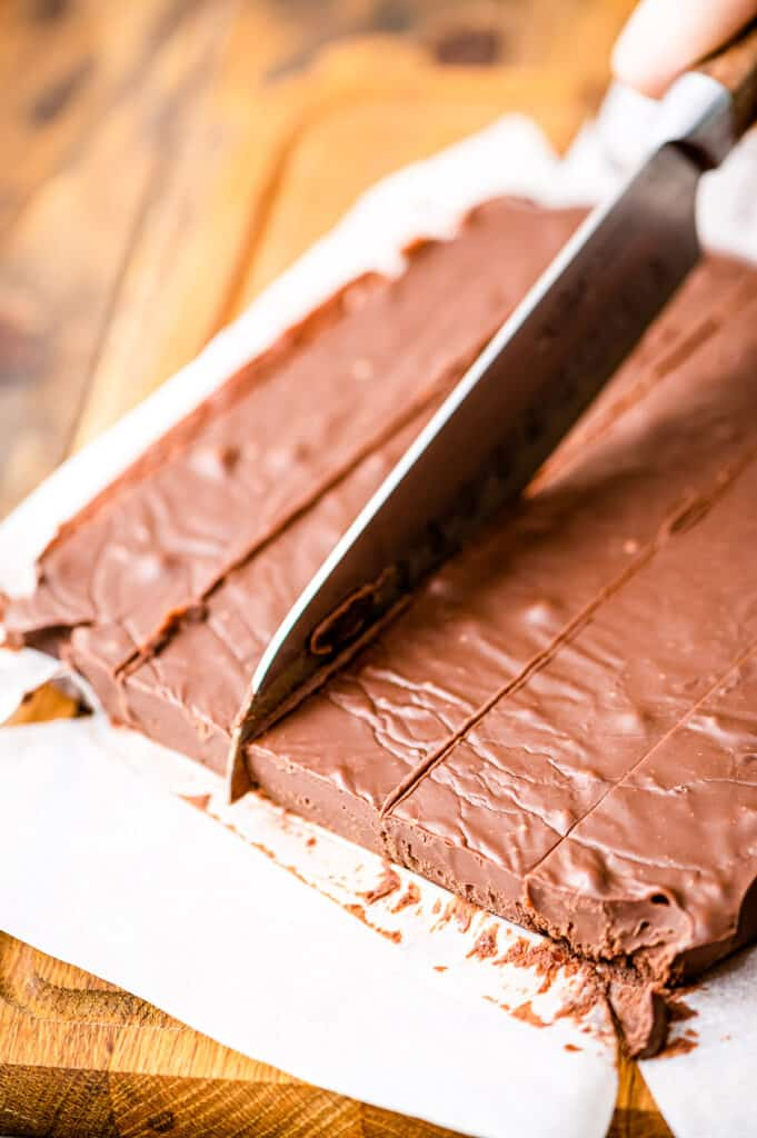 Knife cutting cooled chocolate fudge into piecese