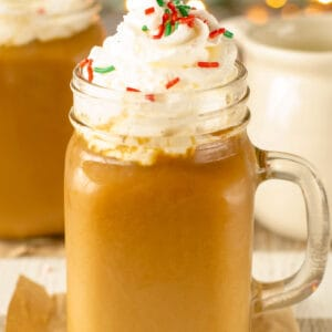 Glass Mug with Christmas Coffee topped with whipped cream and sprinkles