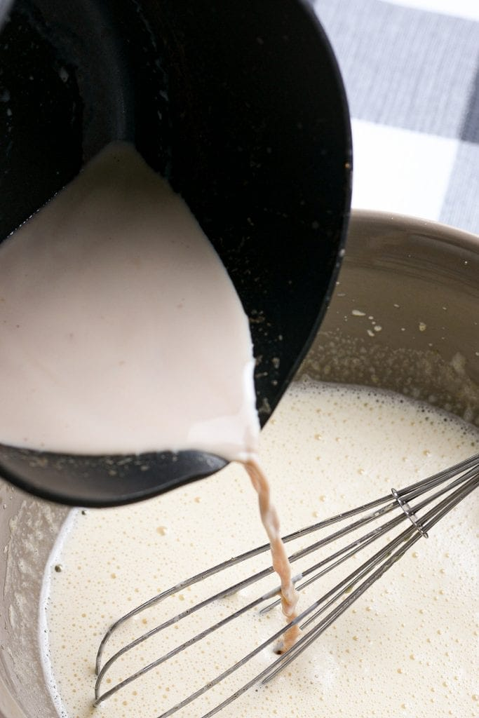 Pouring heated milk into egg mixture for eggnog