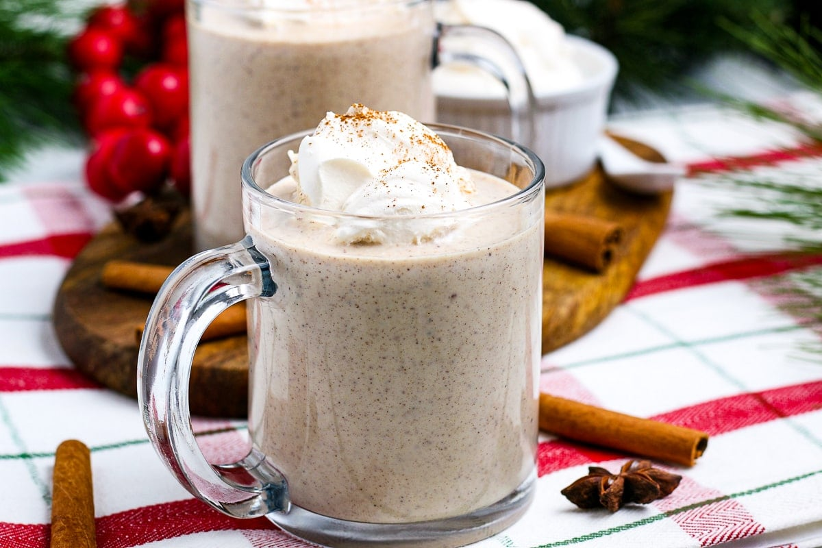 Mug with homemade eggnog topped with whipped cream and more in background