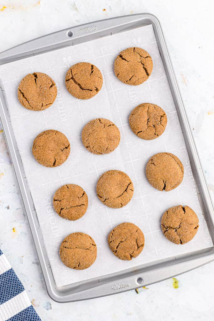 Overhead image of baking sheet with molasses cookies on it baked