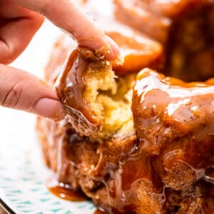 Finger pulling a piece of monkey bread out of pull aparts.