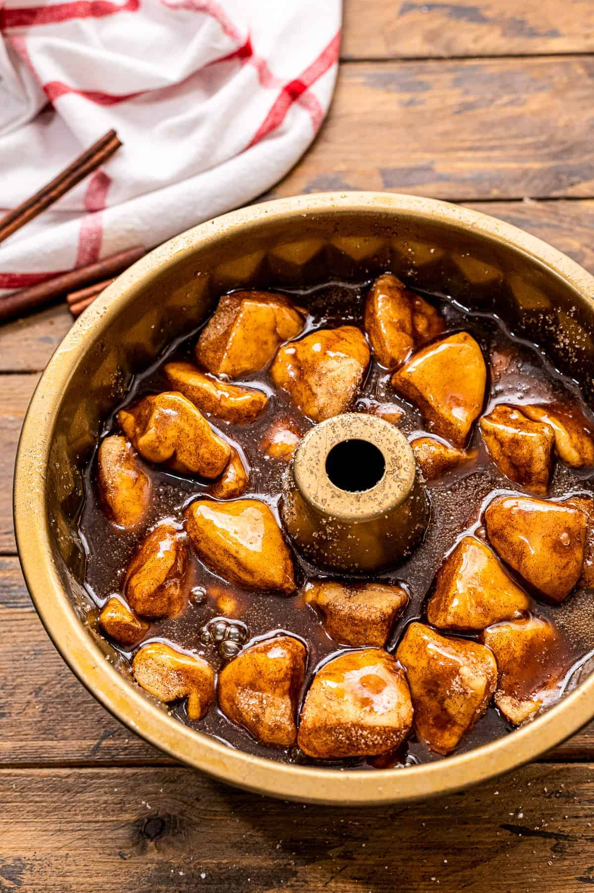 A bundt pan with monkey bread covered with caramel before baking