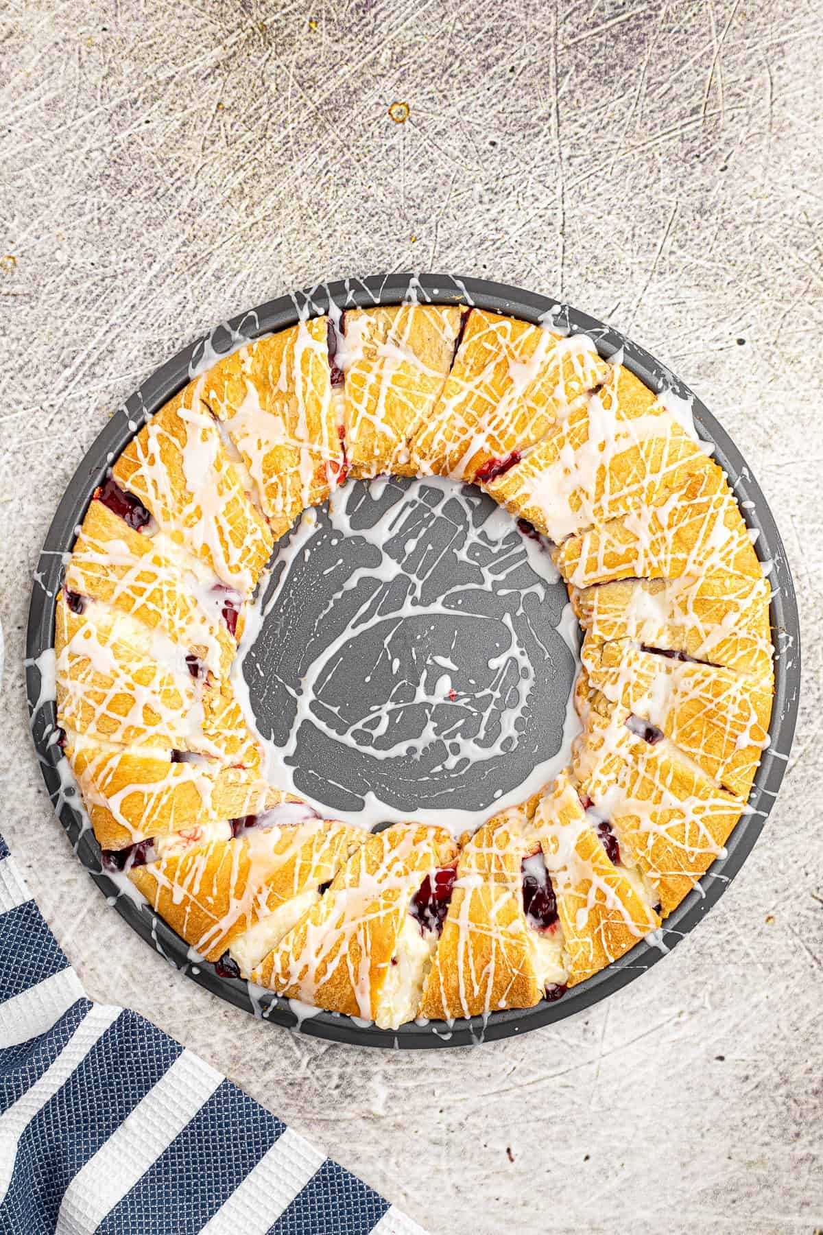 Overhead image of Strawberry Cheesecake Crescent Ring Baked on pizza pan drizzled with icing