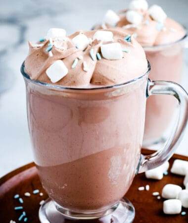 Mug full of Whipped Hot Chocolate topped with marshmallows and sprinkles