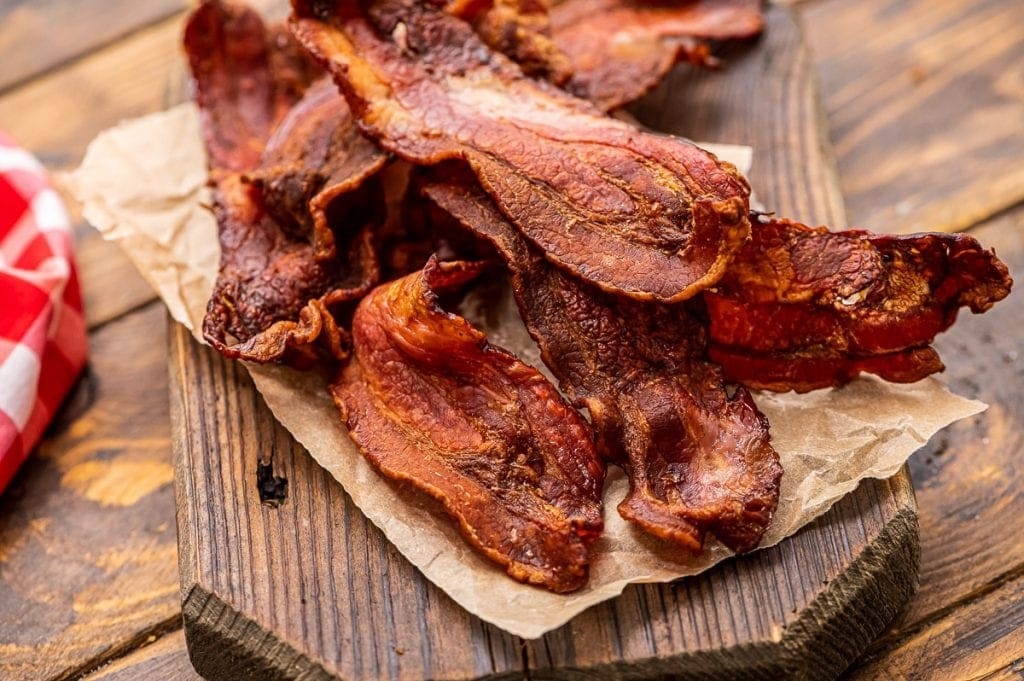 Crispy bacon on paper on top of wood cutting board
