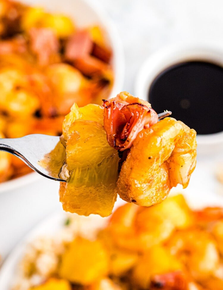 Air Fryer Hawaiian Kabobs on a fork. A piece of pineapple, ham and shrimp coated in BBQ Sauce.