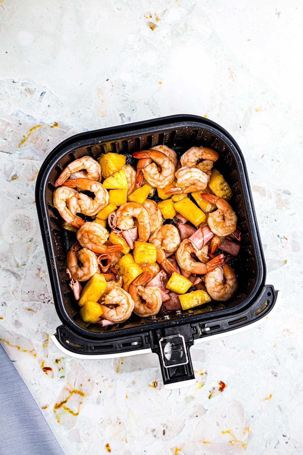 Cooked Hawaiian Shrimp mixture in air fryer basket.
