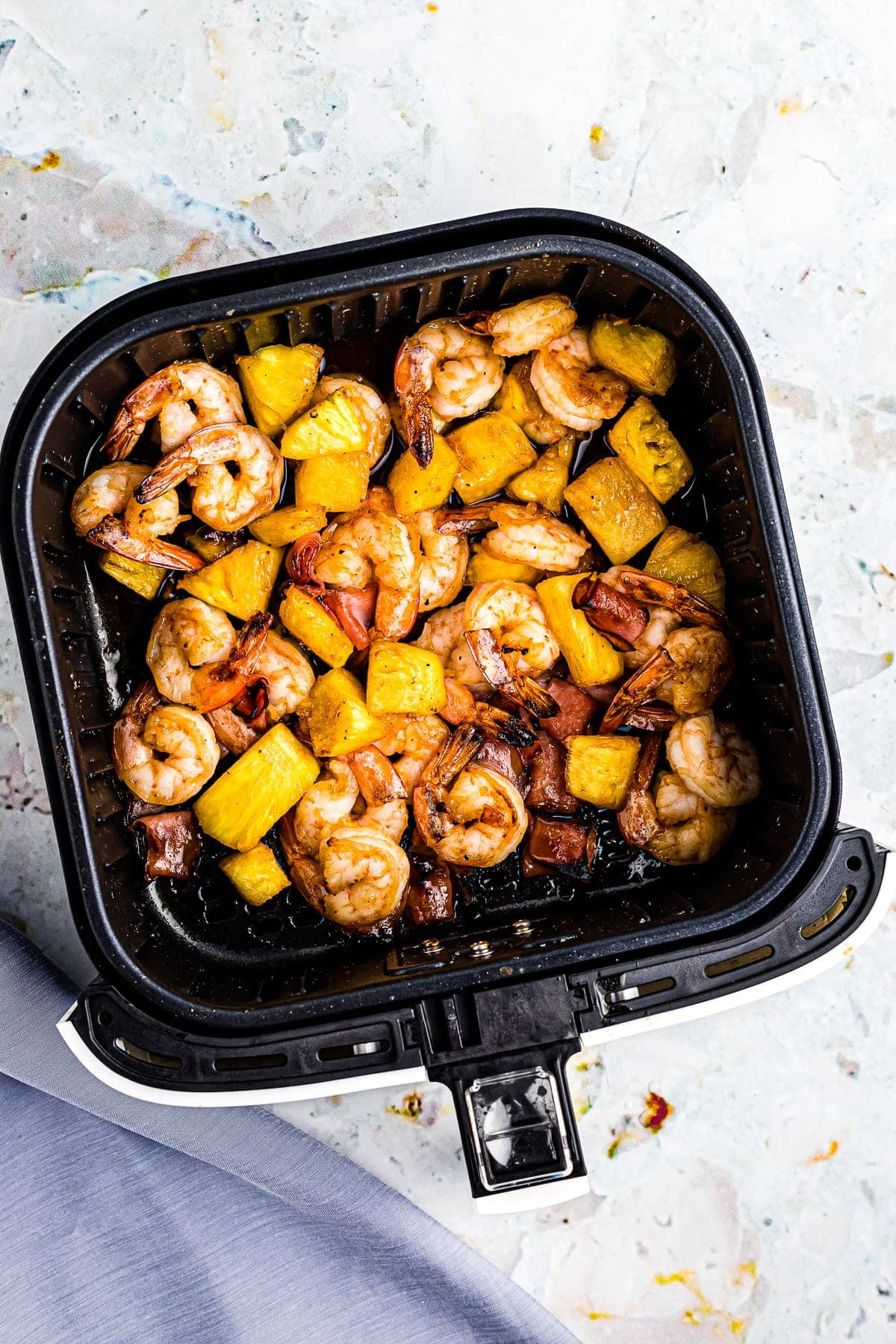 Air Fryer Basket with a mix of pineapple, shrimp and ham in a bbq sauce.