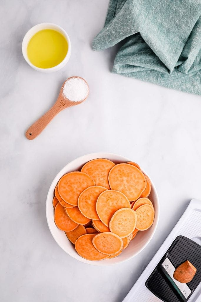 Thinly sliced sweet potatoes in white dish