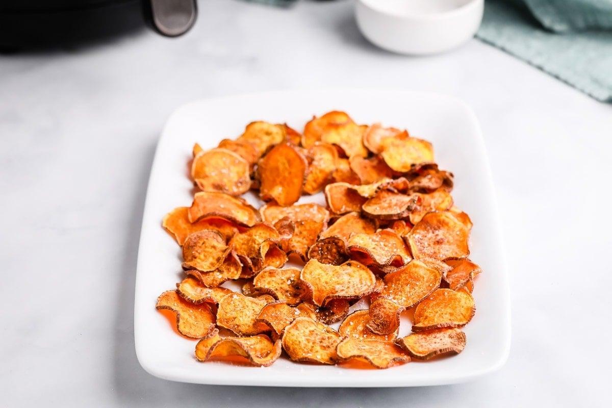 White platter of sweet potato chips seasoned with salt
