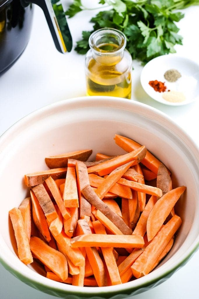 A ceramic bowl with sliced sweet potato fries in it.