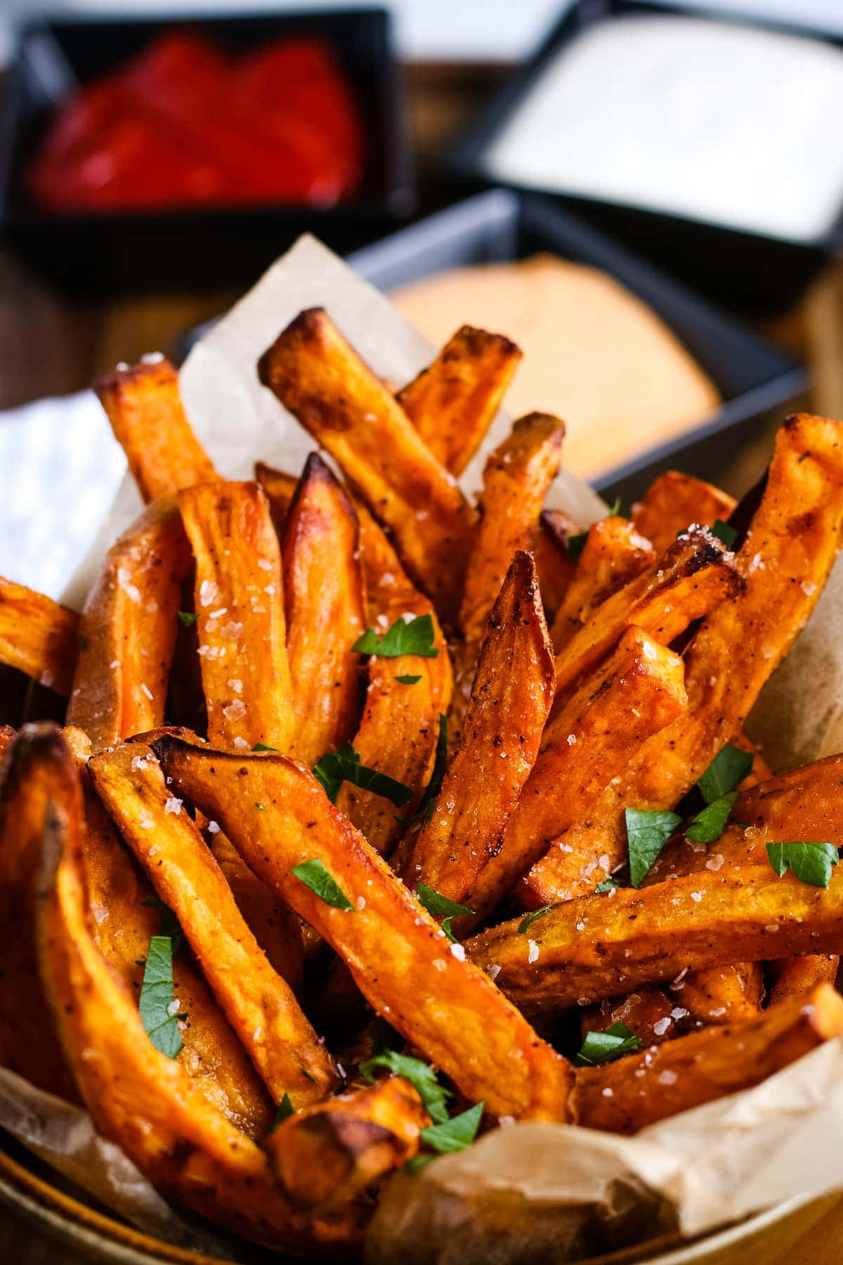 Air Fryer Sweet Potato Fries in a cup and garnished with parsley
