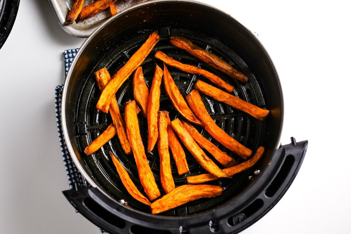An air fryer basket with cooked sweet potatoes fries in it.