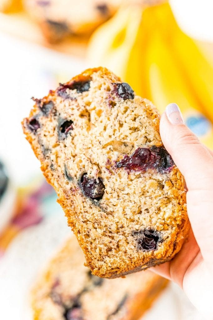 Hand holding a slice of Blueberry Banana Bread.