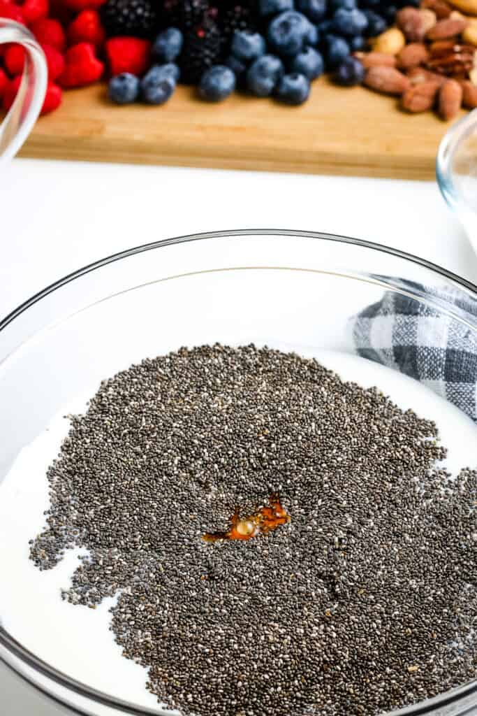 Glass bowl with ingredients to make chia pudding before mixing