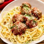 Square Image showing crock pot meatballs served over spaghetti noodles