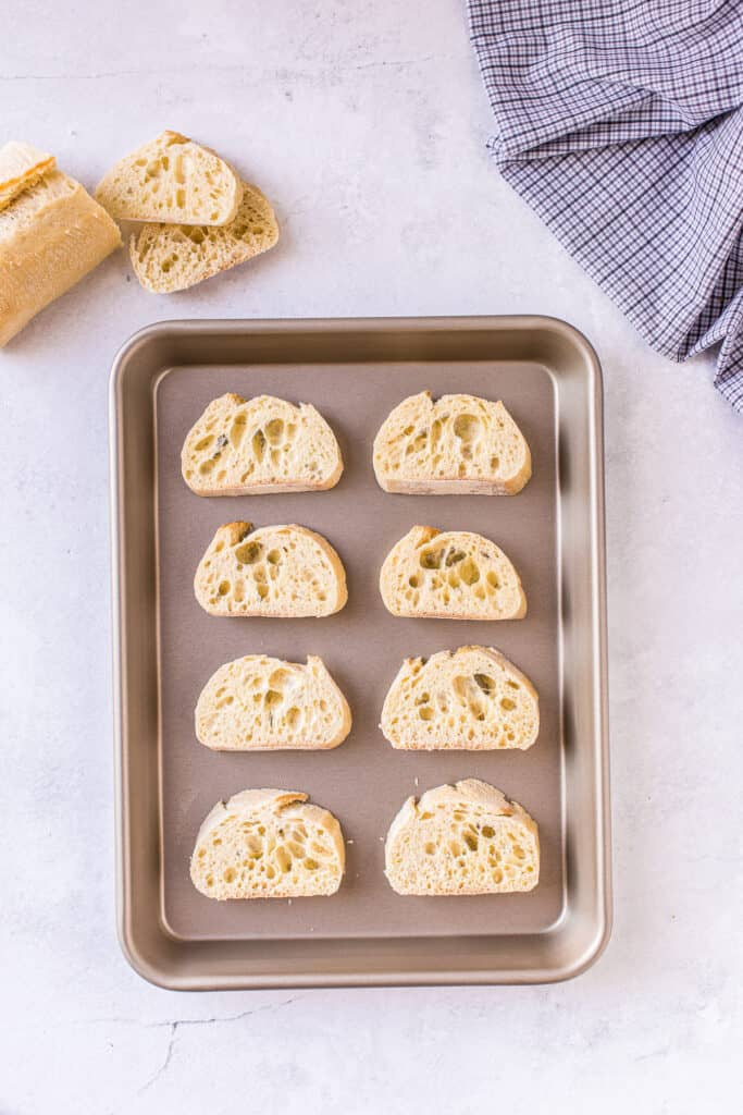 Baguette sliced on baking sheet