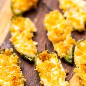 Wood cutting board with baked jalapeno poppers.