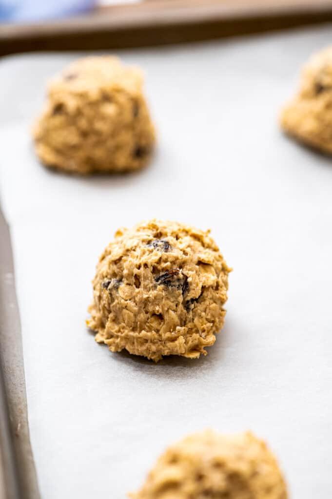 Raw oatmeal raisin cookies on baking sheet